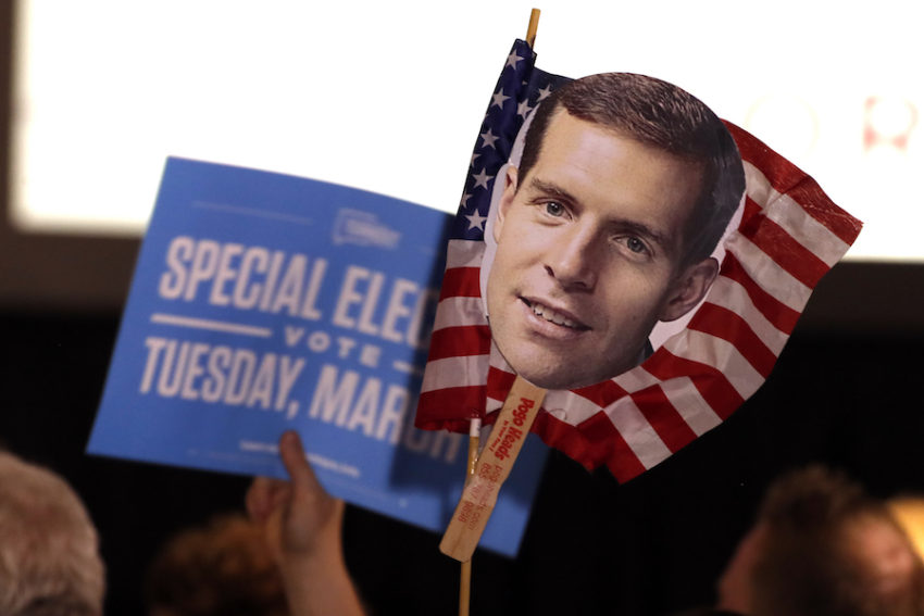 Supporters of Conor Lamb, the Democratic candidate in Pennsylvania's 18th Congressional District, hold signs at a special election event in March. (Gene J. Puskar / AP)