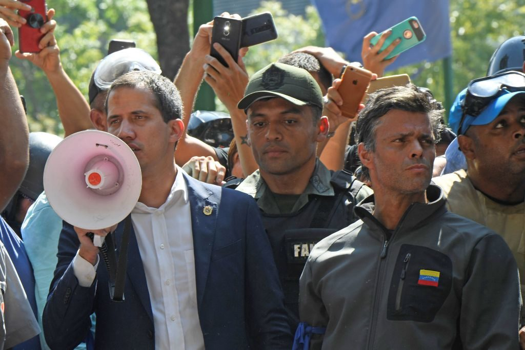 Venezuelan opposition leader and self-proclaimed acting president Juan Guaido (L) speaks to supporters next to high-profile opposition politician Leopoldo Lopez (R), who had been put under home arrest by Venezuelan President Nicolas Maduro's regime, and members of the Bolivarian National Guard who joined his campaign to oust Maduro, in Caracas on April 30, 2019. - Guaido said there is 'no turning back' in the bid to oust Maduro. (Photo by Federico PARRA / AFP)        (Photo credit should read FEDERICO PARRA/AFP/Getty Images)