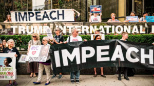 Protesters holding signs calling for Trump's impeachment.