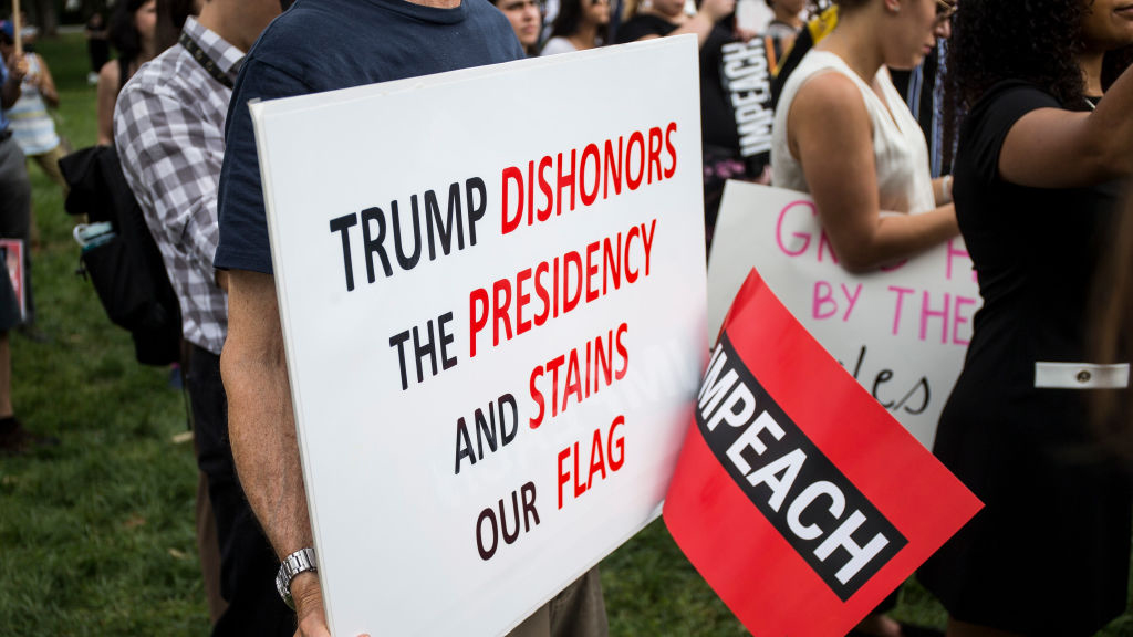 Protesters hold signs calling for Trump's impeachment