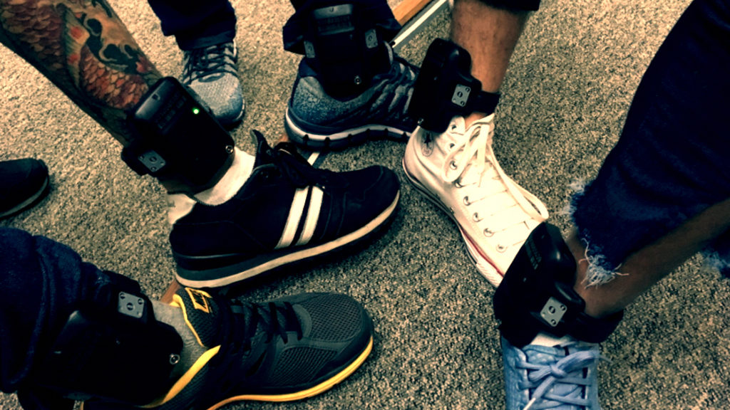 A closeup image of the ankle monitors being worn by five people