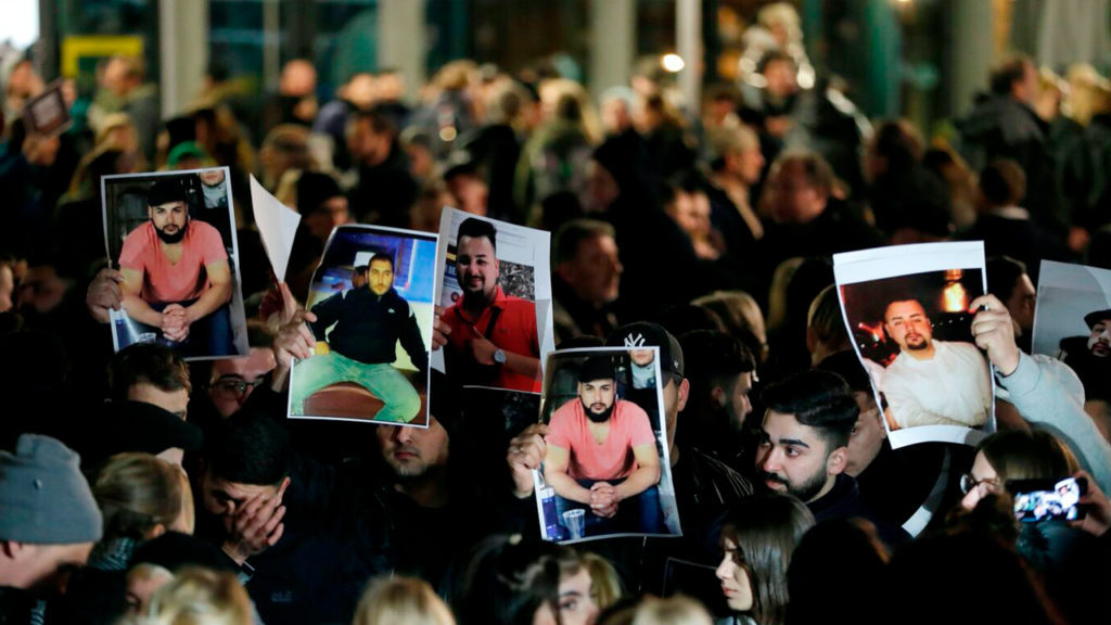 Mourners hold up photos, believed to be of victims, during a vigil close to a crime scene in Hanau, near Frankfurt am Main, western Germany, on February 20, 2020, after at least nine people were killed in two shootings late on February 19, 2020. Odd Andersen/AFP via Getty Images