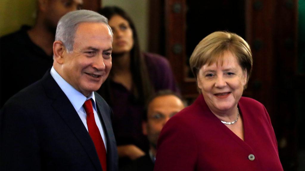 Israeli Prime Minister Benjamin Netanyahu and German Chancellor Angela Merkel walk before a press conference at a hotel in Jerusalem, on October 4, 2018. Menahem KAHANA/AFP/Getty Images