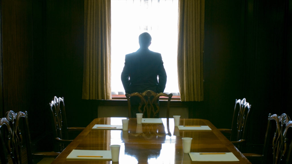 Businessman facing window in meeting room, rear view. Stock photo/Getty Images