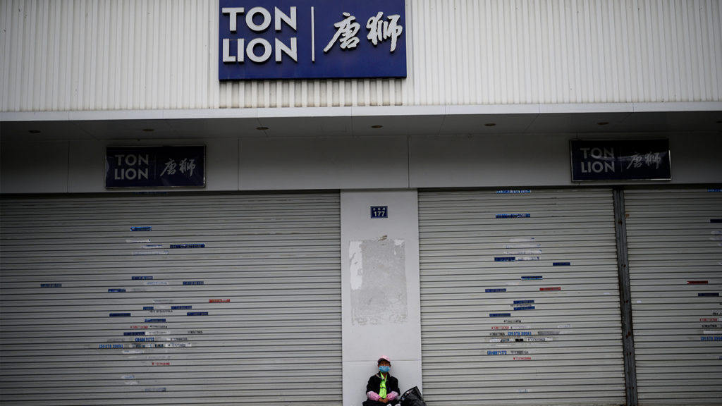 This photo taken on February 27, 2020 shows a man wearing a face mask as he sits along rows of closed shops near the Zhejiang Xuda Shoes Co. factory in Wenzhou. - The number of new cases of the COVID-19 coronavirus in China has declined in recent days, but infections in other countries have gathered pace. (Photo by NOEL CELIS / AFP) (Photo by NOEL CELIS/AFP via Getty Images)