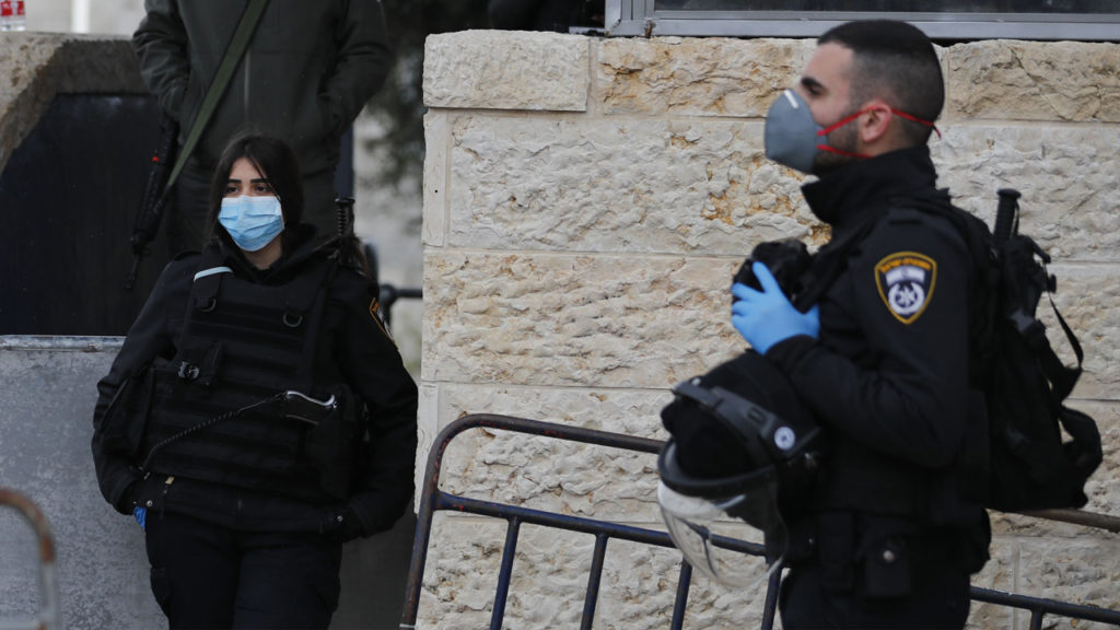 Members of the Israeli security forces, wearing protective face masks, stand guard in front of the Damascus gate in Jerusalem's Old City, after Israel banned non-essential movement and ordered the closure of all leisure and entertainment venues in a bid to stem the spread of the novel coronavirus, on March 20, 2020. Ahmad Gharabli/AFP via Getty Images