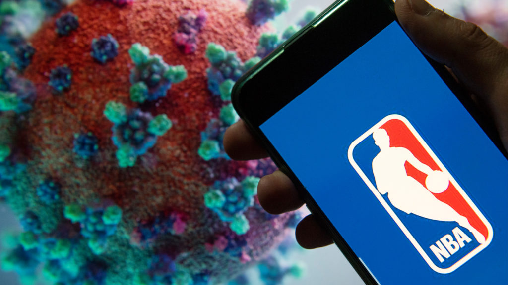 NBA men's professional basketball league logo seen displayed on a smartphone with a computer model of the COVID-19 coronavirus on the background. Budrul Chukrut/SOPA Images/LightRocket via Getty Images