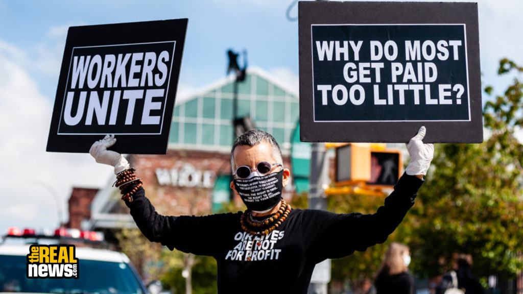 A car caravan protester shows solidarity with essential workers, who are put at risk every day with low pay and without necessary protective gear outside a Whole Foods store in Brooklyn, New York, on May 1, 2020. Gabriele Holtermann-Gorden/Sipa USA via REUTERS