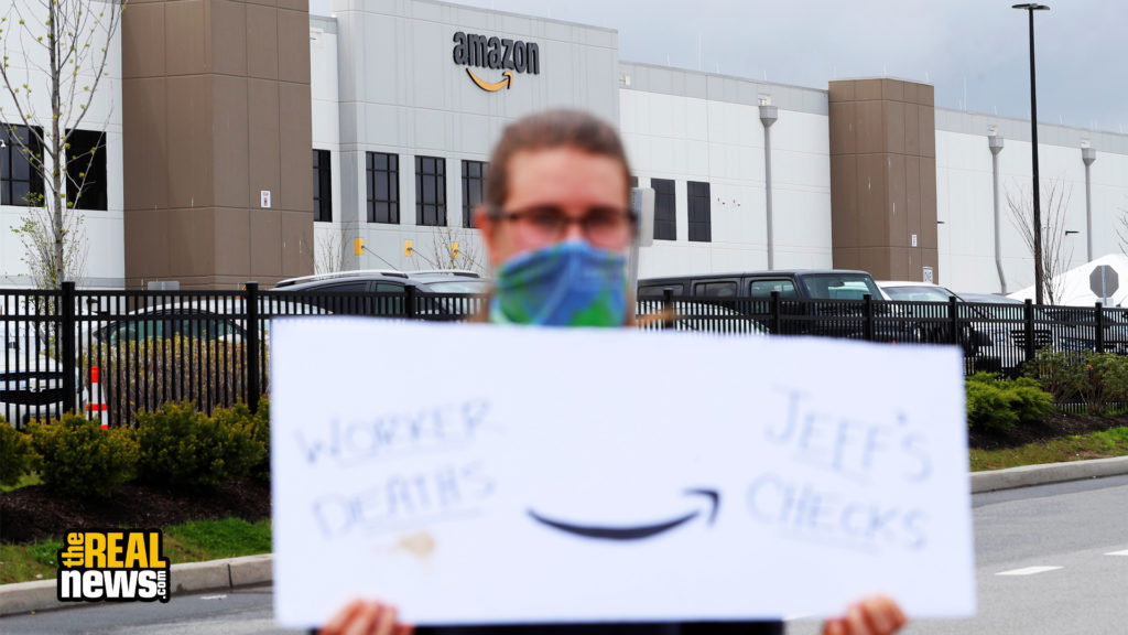 A demonstrator holds a sign during a protest outside of an Amazon warehouse as the outbreak of the coronavirus disease (COVID-19) continues in the Staten Island borough of New York U.S., May 1, 2020. Lucas Jackson/REUTERS