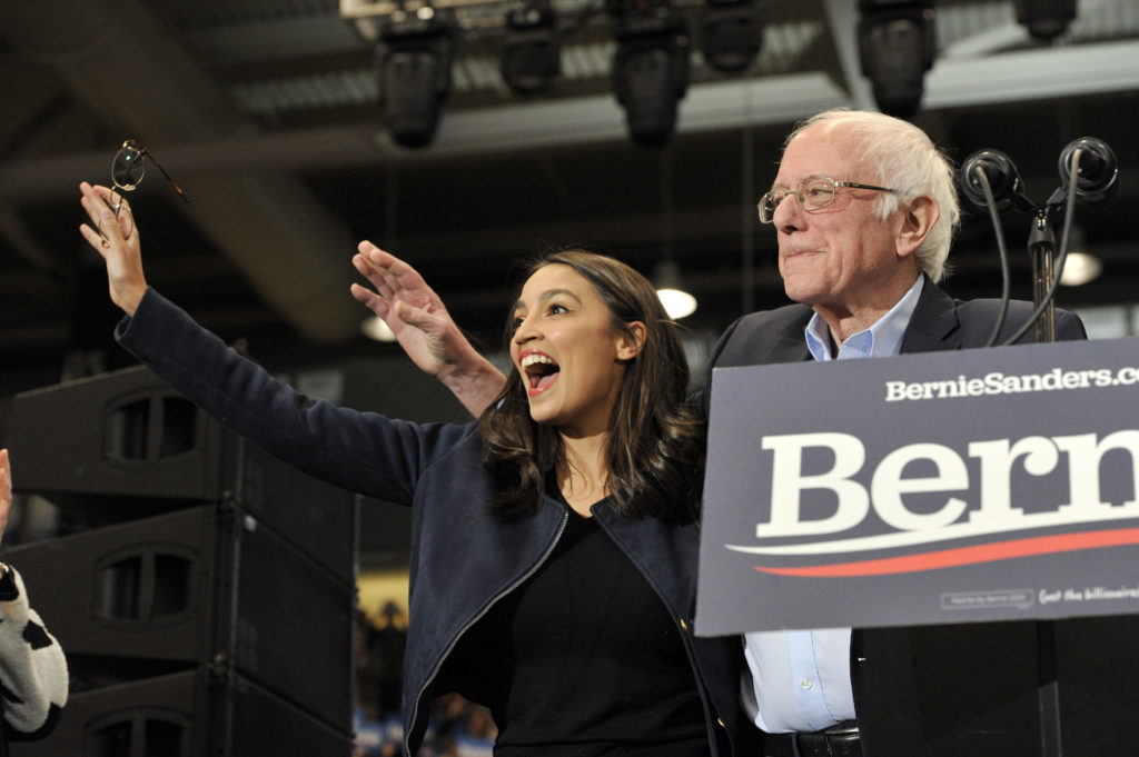 Congresswoman Alexandria Ocasio-Cortez and Presidential Candidate Vermont Senator Bernie Sanders wave to his supporters at rally at the University of New Hampshire in Durham, New Hampshire on February 10, 2020. (Photo by Joseph Prezioso / AFP) (Photo by JOSEPH PREZIOSO/AFP via Getty Images)